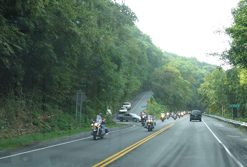 A two lane road cuts between hills covered densely with trees; a group of motorcycles heads in the opposite direction of the truck