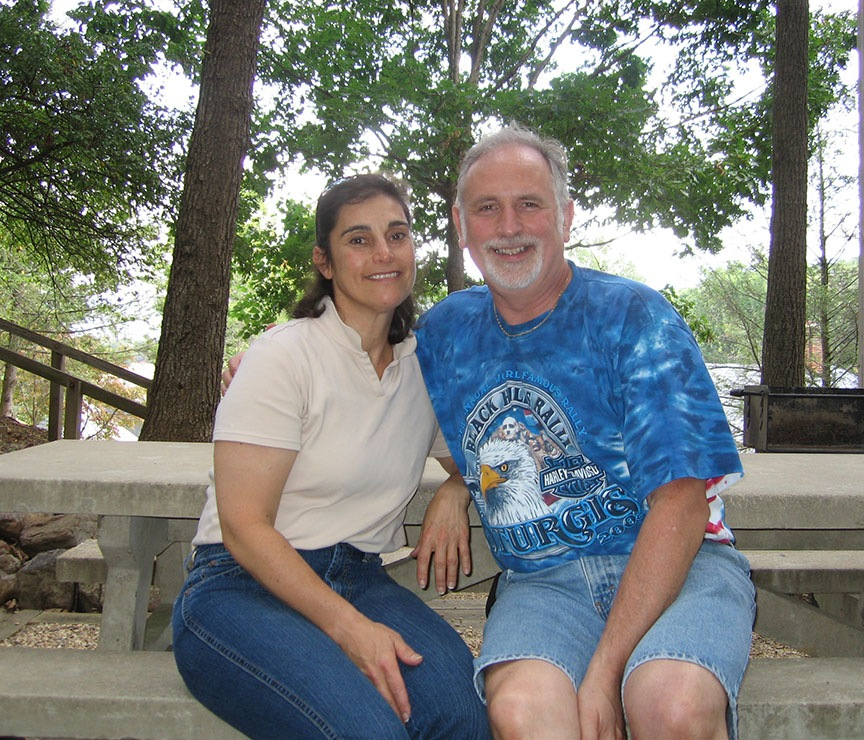 Lisa and Rick sit at a concrete picnic table, smiling to the camera; behind them are trees