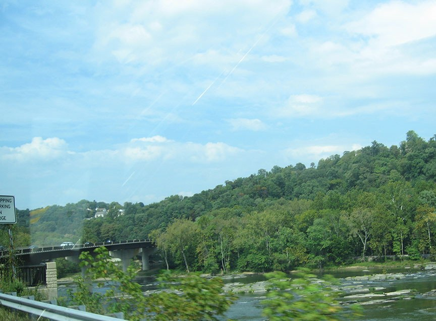 River runs along the highway; a bridge stands over the river in the distance to a densely covered hill