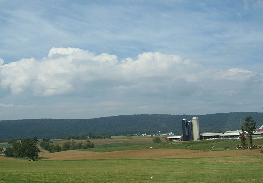 A series of red farm buildings with white roofs stand among rolling farmlands; low hills stand in the distance