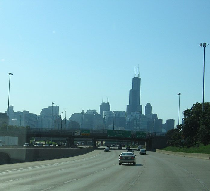 Freeway stretches in front of the truck, leading it to the downtown Chicago skyline in the distance