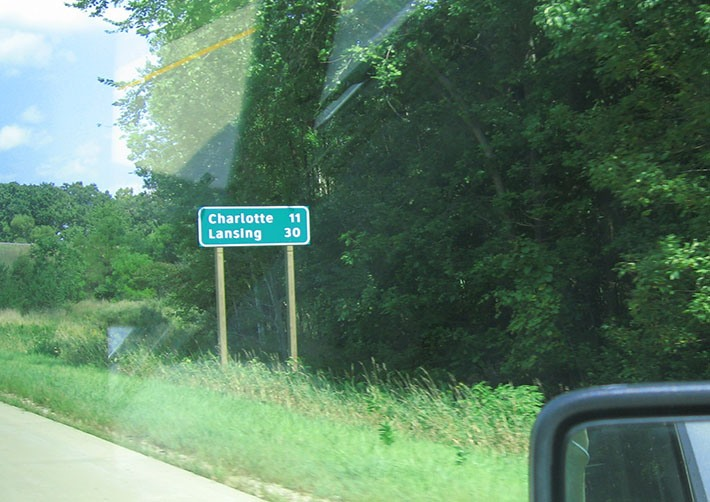 A freeway distance sign stands on the shoulder of the free way, it reads Charlotte 11, Lansing 30