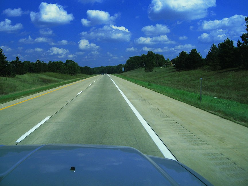 Two lanes of road stretch in front of the truck between grassy shoulders, above is a blue sky filled with fluffy white clouds