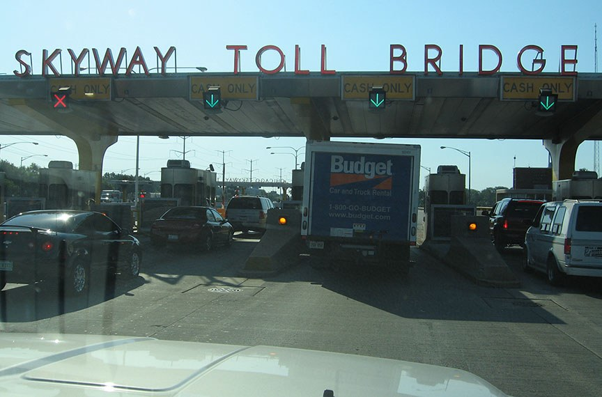Cars line up at the Chicago Skyway Toll Bridge, bright blue sky stretches out behind it