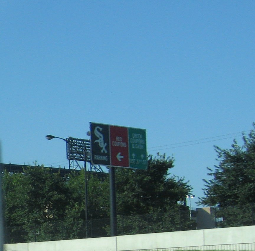 A directional sign for U.S. Cellular Field stands just off the highway with arrows to parking, red coupons, and green coupons.