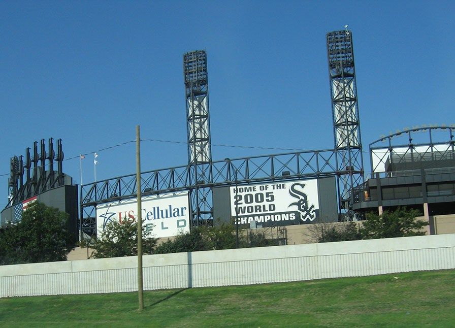"U.S. Cellular Field stands adjacent to the freeway displaying signs on the side that read ""Home of the 2005 World Champions"" and ""U.S. Cellular Field"""