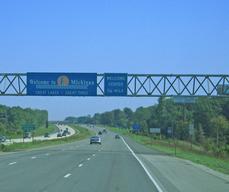 A blue Welcome to Michigan sign stretches over the freeway, a blue sky stretches beyond it