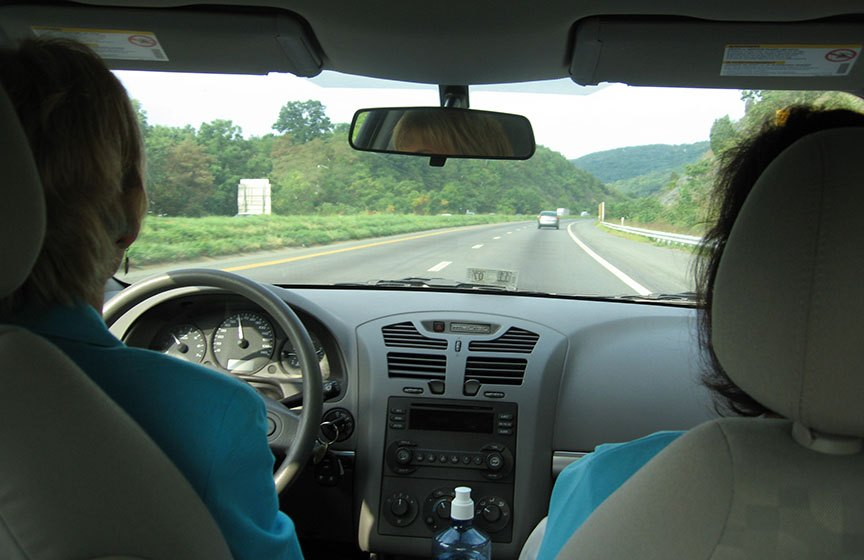 The driver and passenger of the car sit facing forward, the road stretching in front of them through the front windshield; trees stand along the road