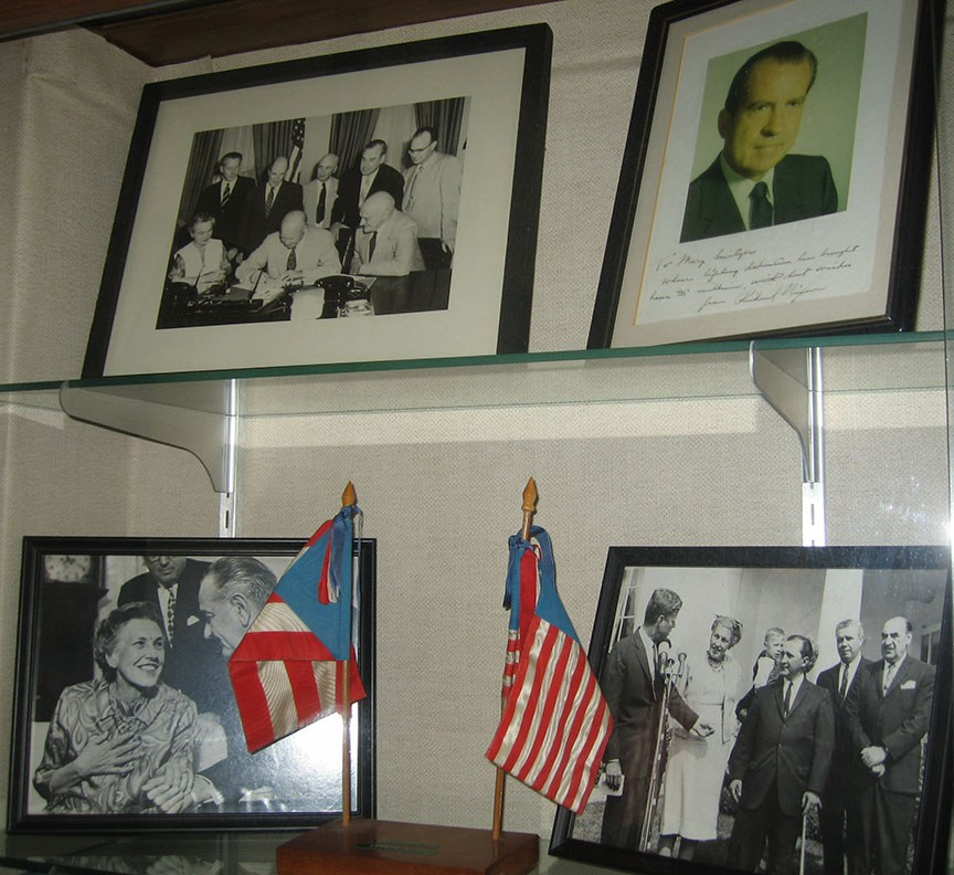 Four photos stand on glass shelves; in the photos are Mary Switzer along with various former presidents and people