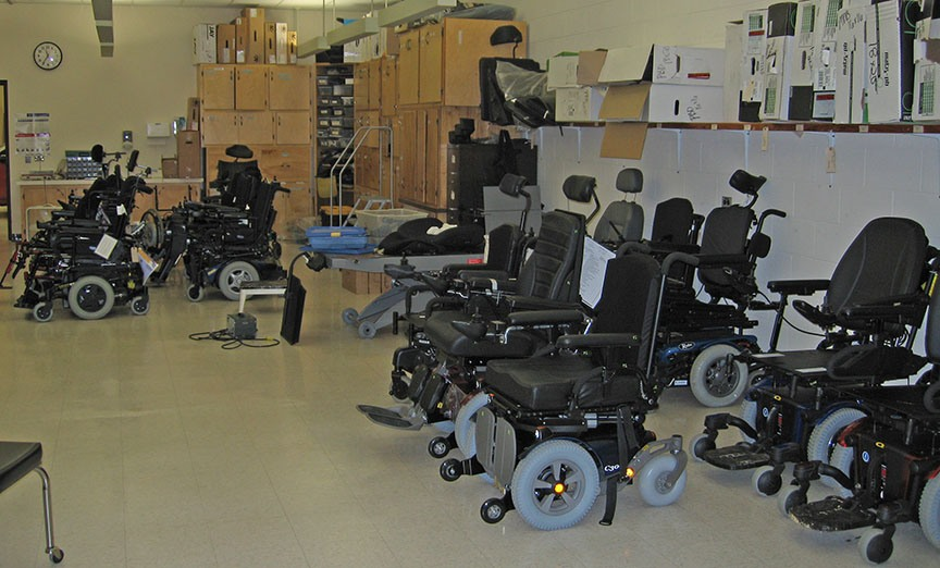 Various  wheelchairs, many motorized, are parked in a room, ready for use