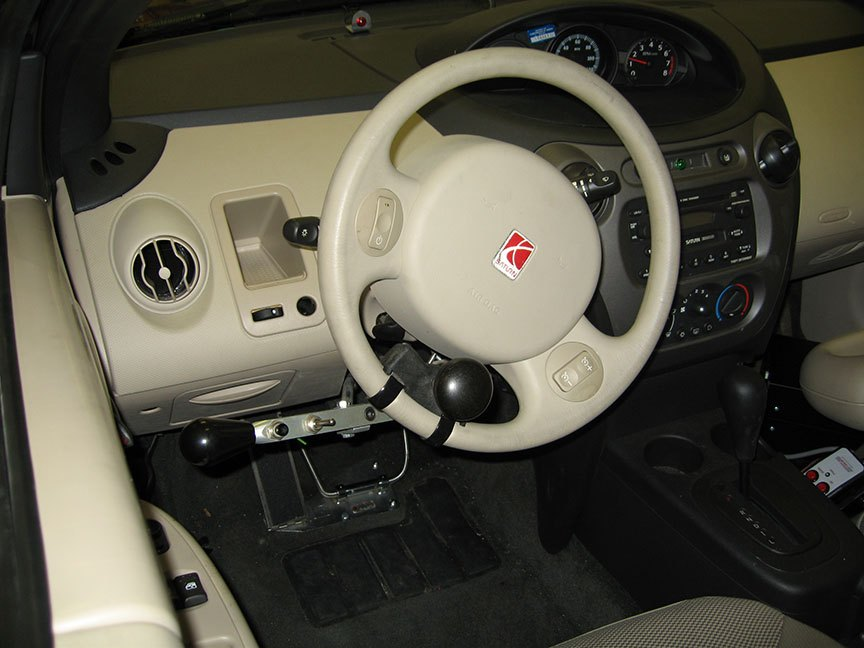 The interior of a car with a modified steering wheel that has additional handles and knobs