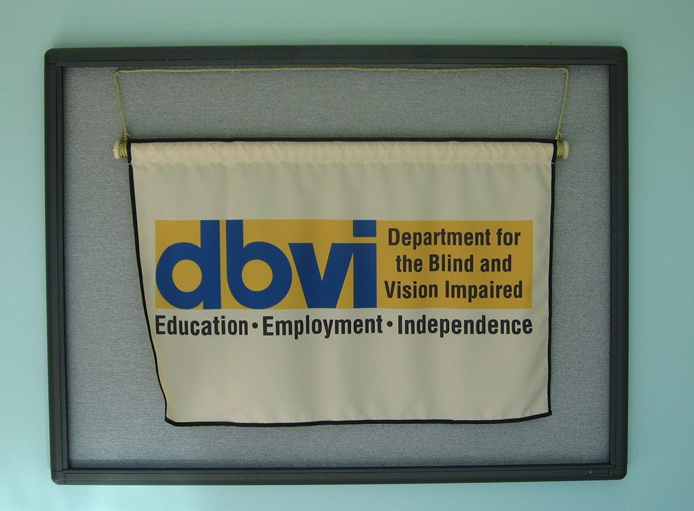 "A banner reads ""DBVI Department for the Blind and Vision Impaired; Education, Employment, Independence"" and hangs on a corkboard against a blue wall."