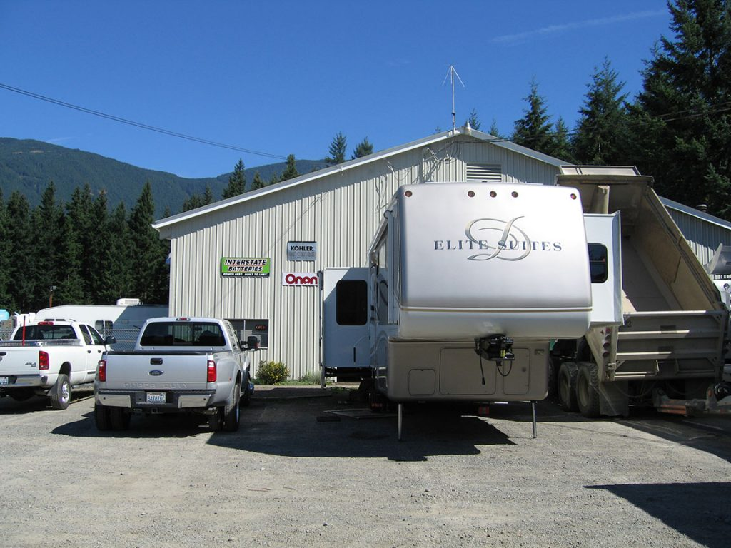 A silver duallie pick-up truck and a set up Elite Suites RV are parked in front of a one story white building with a green sign that says Interstate Batteries. A bright blue sky is over the tops of green trees and foothills behind the building.