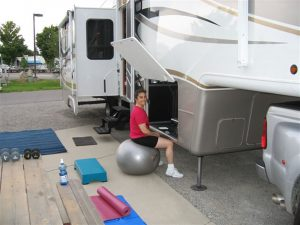 Lisa Gifford sits on a silver exercise ball outside the camped RV while working on her laptop. Behind her, other exercise gear including hand weights and yoga mats are laid out for use.