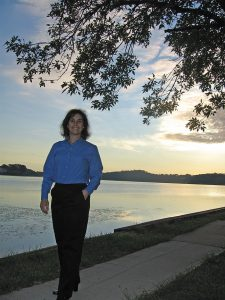 Lisa stands on the sidewalk, smiling to the camera; Chesapeake Bay stretches out behind her