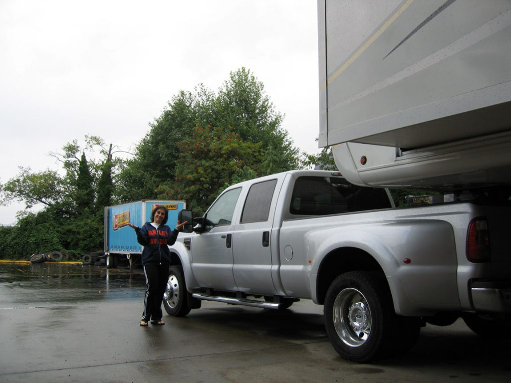 Lisa Gifford in a blue Harley Davidson sweatshirt stands at the front of a silver pick-up truck. In the background, a blue Les Schwab Tire container stands in front of a tree line.