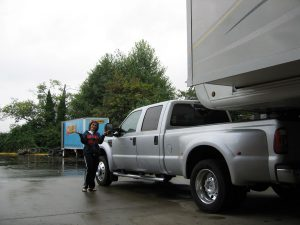 Lisa Gifford stands next to a silver pick-up truck and RV parked under an awning. The RV is parked and extended for camping. A Les Schwab Tire sign can be seen in the background as well as trees.