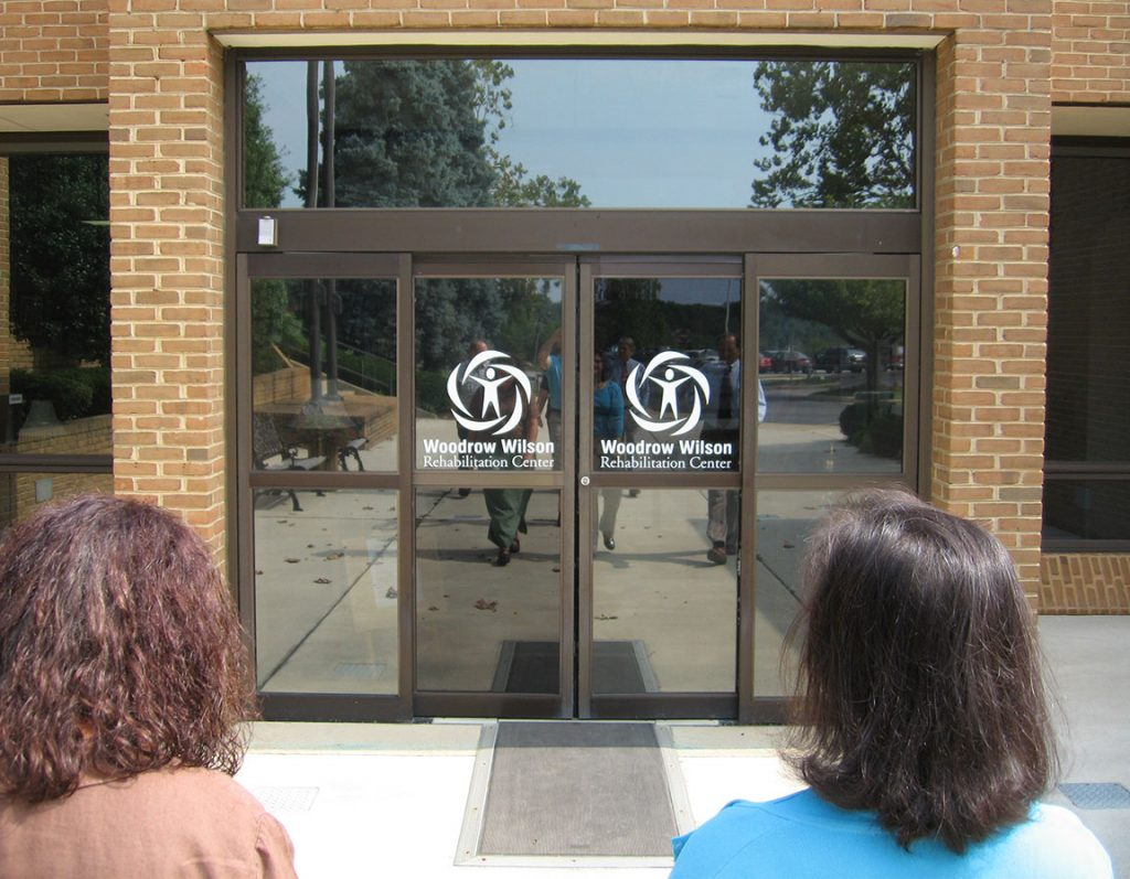A group of individuals walks toward the glass sliding doors of the Woodrow Wilson Rehabilitation Center; the backs of two heads frame the doors