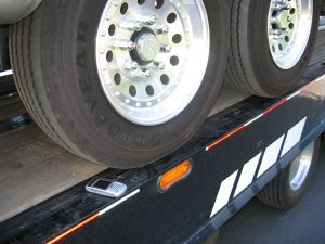 A Blackberry phone sits next to the wheels of the RV and precariously near the edge of the flatbed to demonstrate the mere inches the wheels are from the edge of the flatbed.
