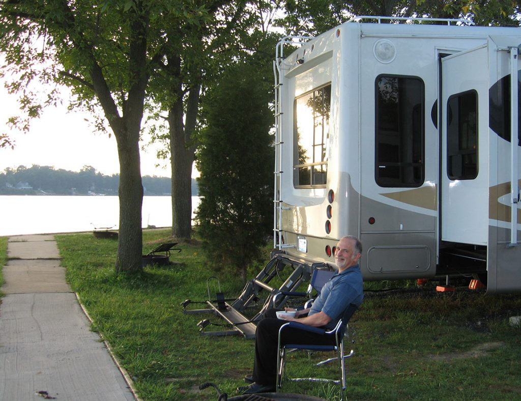Rick sits in a camping chair outside; the RV is behind him as is the Chesapeake Bay