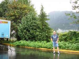 Rick Gifford stands in front of green trees and bushes with Mt. Si in the background surrounded by grey mist. A blue Les Schwab Tires container is to his right.