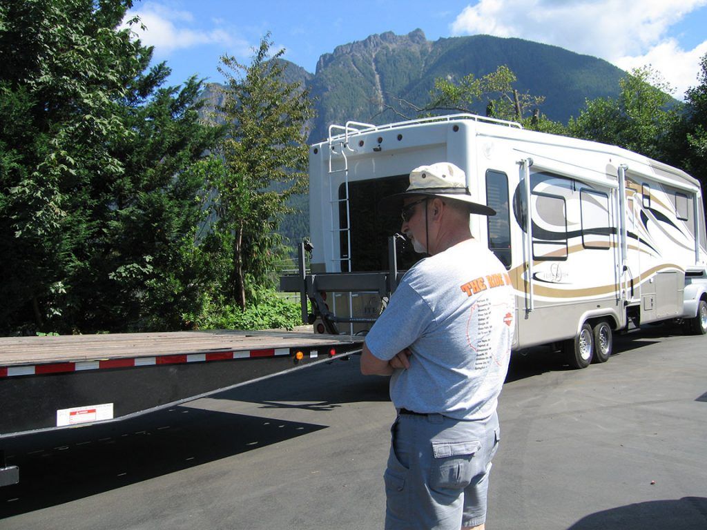 Rick Gifford stands in profile looking at the trailer of the flatbed tow truck. The RV is lined up to the bed of the flatbed tow truck. Mt. Si is in the distance under bright blue skies.