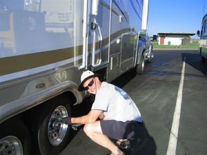 Rick Gifford smiles at the camera while crouched next to the wheel of the RV with a tool in hand while it is parked at a rest area.