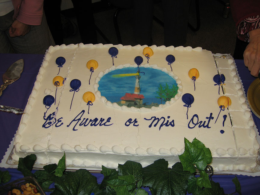 "A cake decorated with a picture of a lighthouse and yellow and blue balloons reads ""Be Aware or Mis Out"""