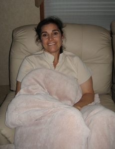 Lisa Gifford sits in a recliner in the RV under a fuzzy blanket and smiles to the camera
