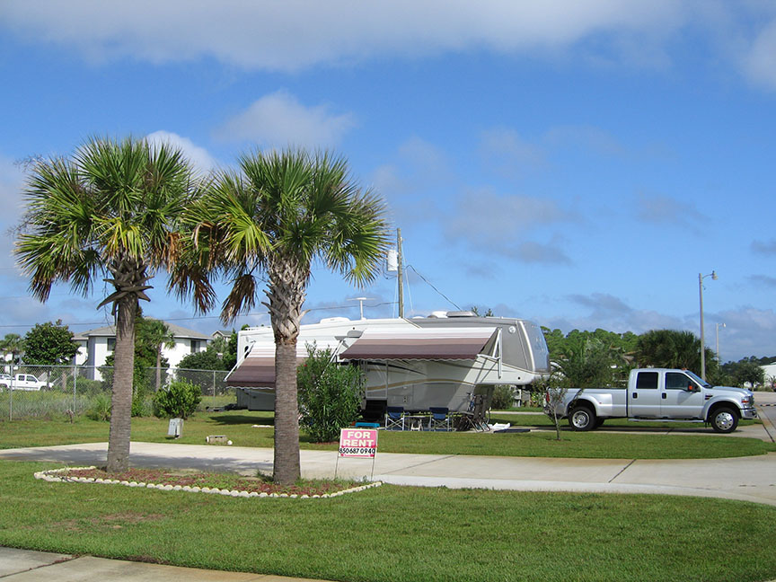 A silver truck is attached to an RV at an RV site in Florida; palm trees stand in front of the RV, and blue skies stretch out overhead